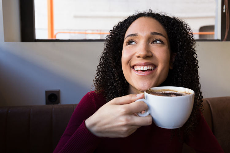 Smiling Young Woman With Coffee Cup Looking Away While Sitting At Cafe