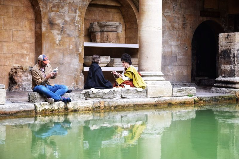 Traveling in Bath Roman Bath History Sitting Tourism Architecture Arch Travel Destinations Men Day Travel Real People Old Ruin Full Length Water Togetherness Religion Architectural Column Women Built Structure Ancient Vacations United Kingdom
