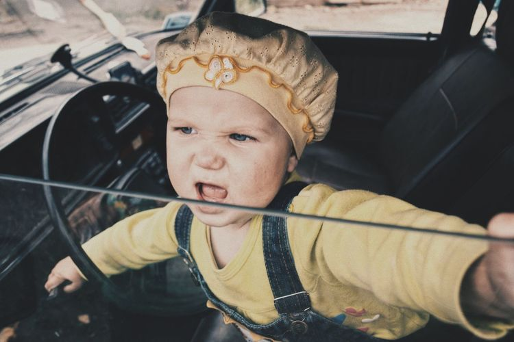High angle view of cute baby girl in car seen through window