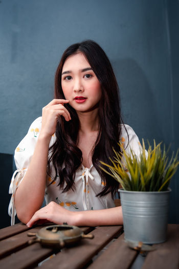 Portrait of beautiful young woman sitting on table