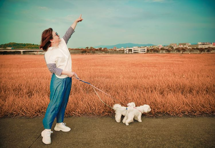 Woman pointing while standing with dogs on road