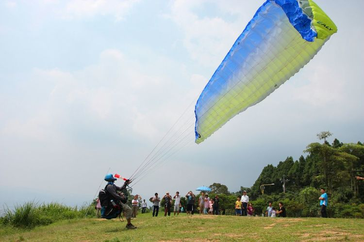 Man Preparing For Paragliding While People Looking At Him