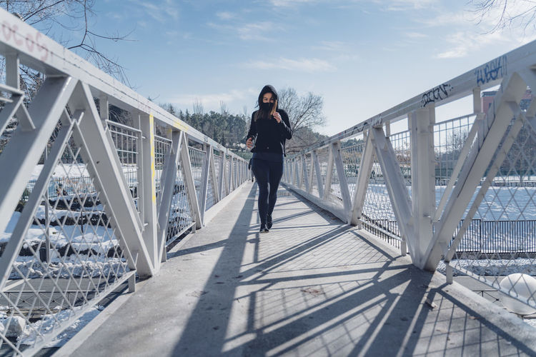 Full length portrait of young woman standing on footbridge