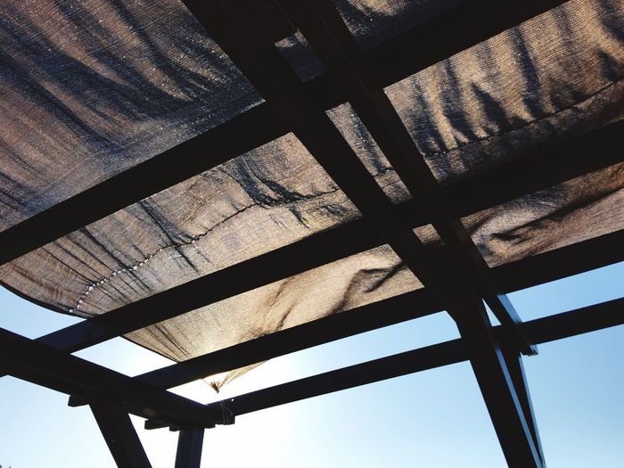 Low angle view of canvas textile on gazebo against sky