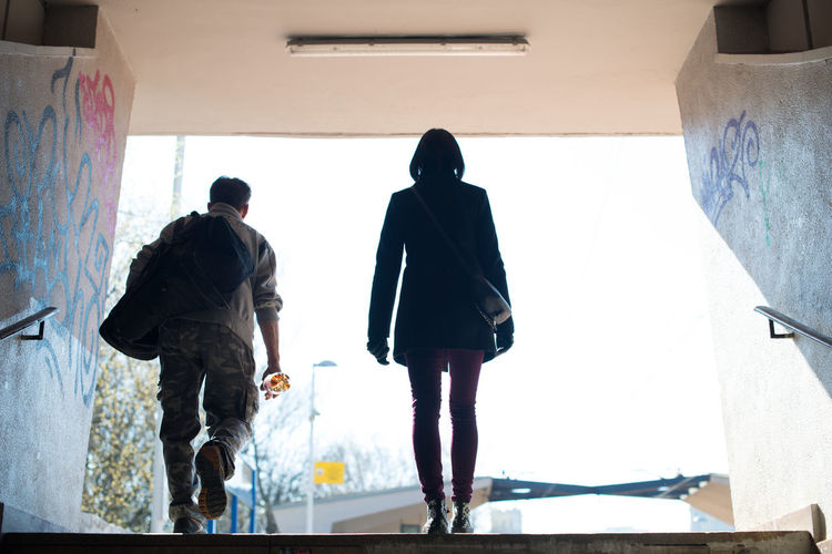 Rear view of man and woman walking on steps