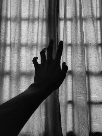 Shadow of person hand on curtain