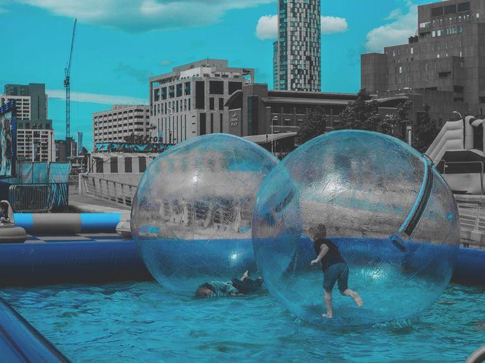 Digital composite image of people in swimming pool against buildings in city
