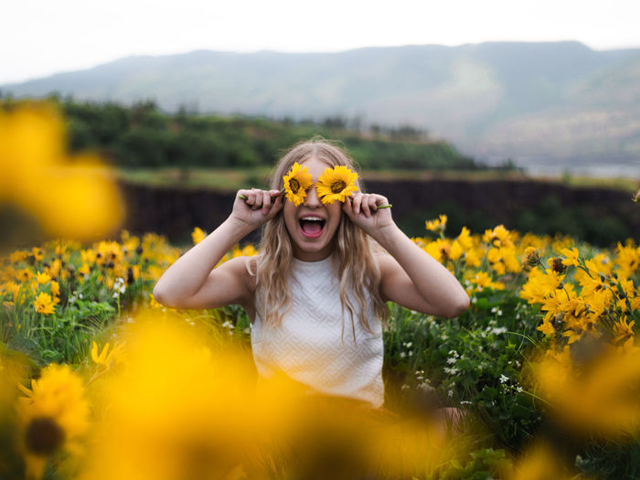 Excited woman shouting while holding flowers over eyes by plants against sky