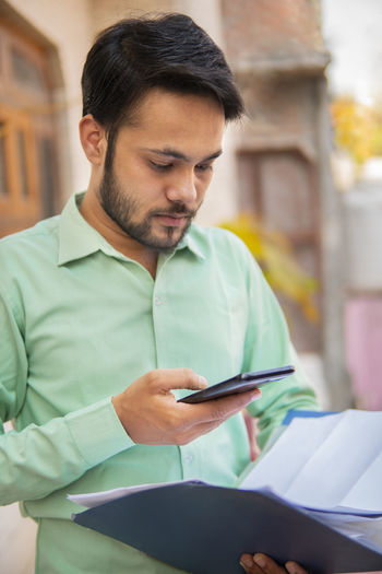 Mid adult man using mobile phone