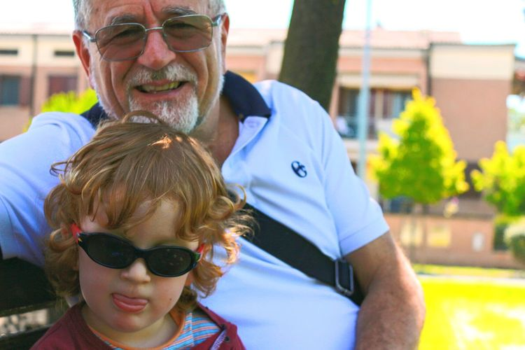 Portrait of grandfather mature man wearing sunglasses sitting on bench with nephew