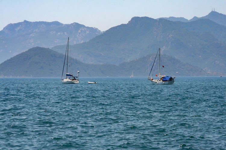 Sailboats on sea against mountains