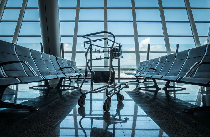 Trolley And Chairs In Airport Against Sky
