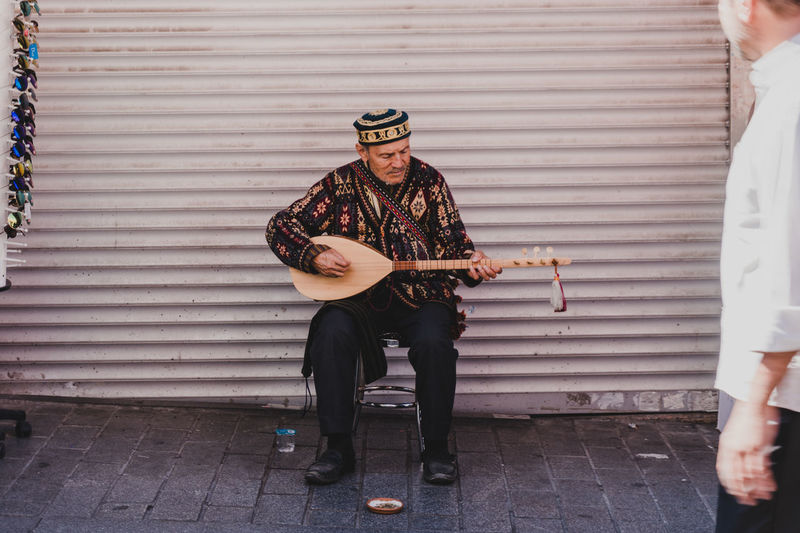 An old man strums a traditional string instrument in a back alley in Istanbul. - IG: @LostBoyMemoirs (All photos taken on Sony A6300 and edited in Lightroom). Istanbul Turkey Turkish EyeEm Best Shots The Week on EyeEm Streetwise Photography Streetphotography Street Photography People People Watching people and places Travel String Instrument Arts Culture And Entertainment Musical Equipment Real People Analogue Sound The Art Of Street Photography