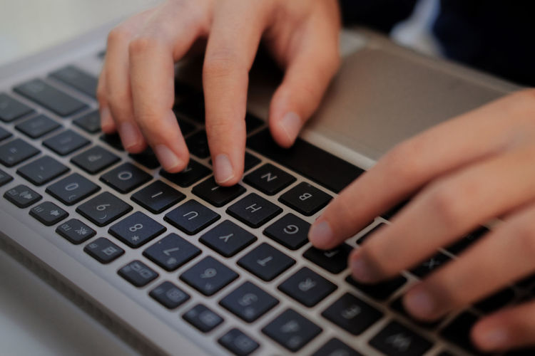 Cropped hands of person using laptop