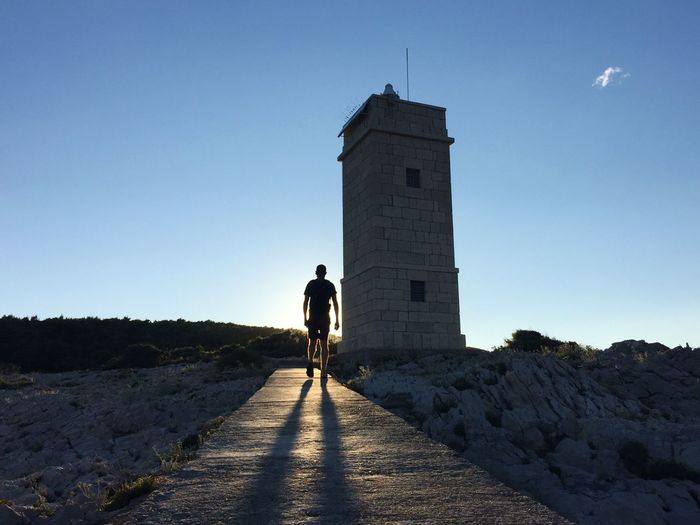 Walking into the sun Sun Silhouette Sunset Golden Hour Light And Shadow Lighthouse Korčula Croatia Travel Travel Photography Man Sunset Silhouettes Showcase July People Together Hidden Gems