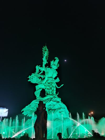 Low angle view of illuminated statue against sky at night