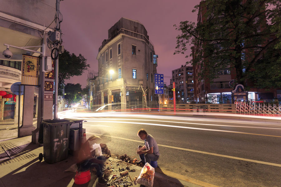 Two men working late at night under the streetlight Adapted To The City Adult Architecture Automobile China City City Life City Street Cityscape Dusk Glow Guangzhou Illuminated Long Exposure Man Motion Motion Blur Night People Road Sky Street Transportation Vehicle Working