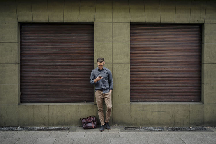 Full length of young man standing against closed shutter