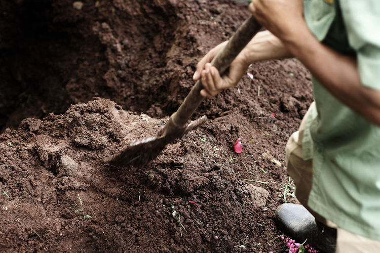 Low section of man digging mud