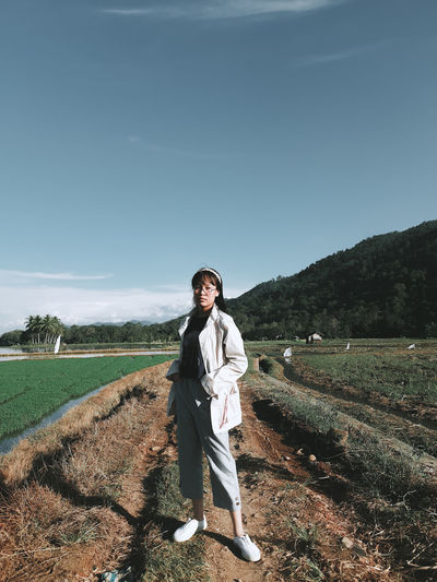 Full length portrait of young woman standing on field against sky