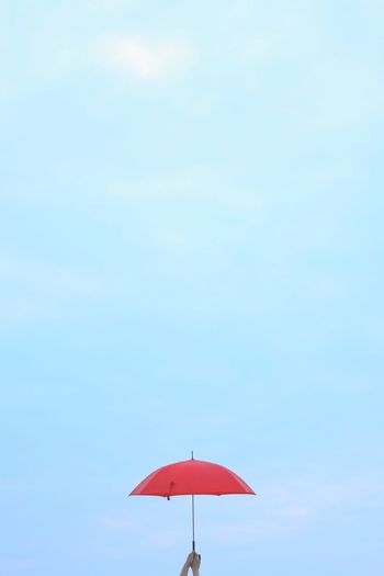 Cropped hand holding umbrella against sky