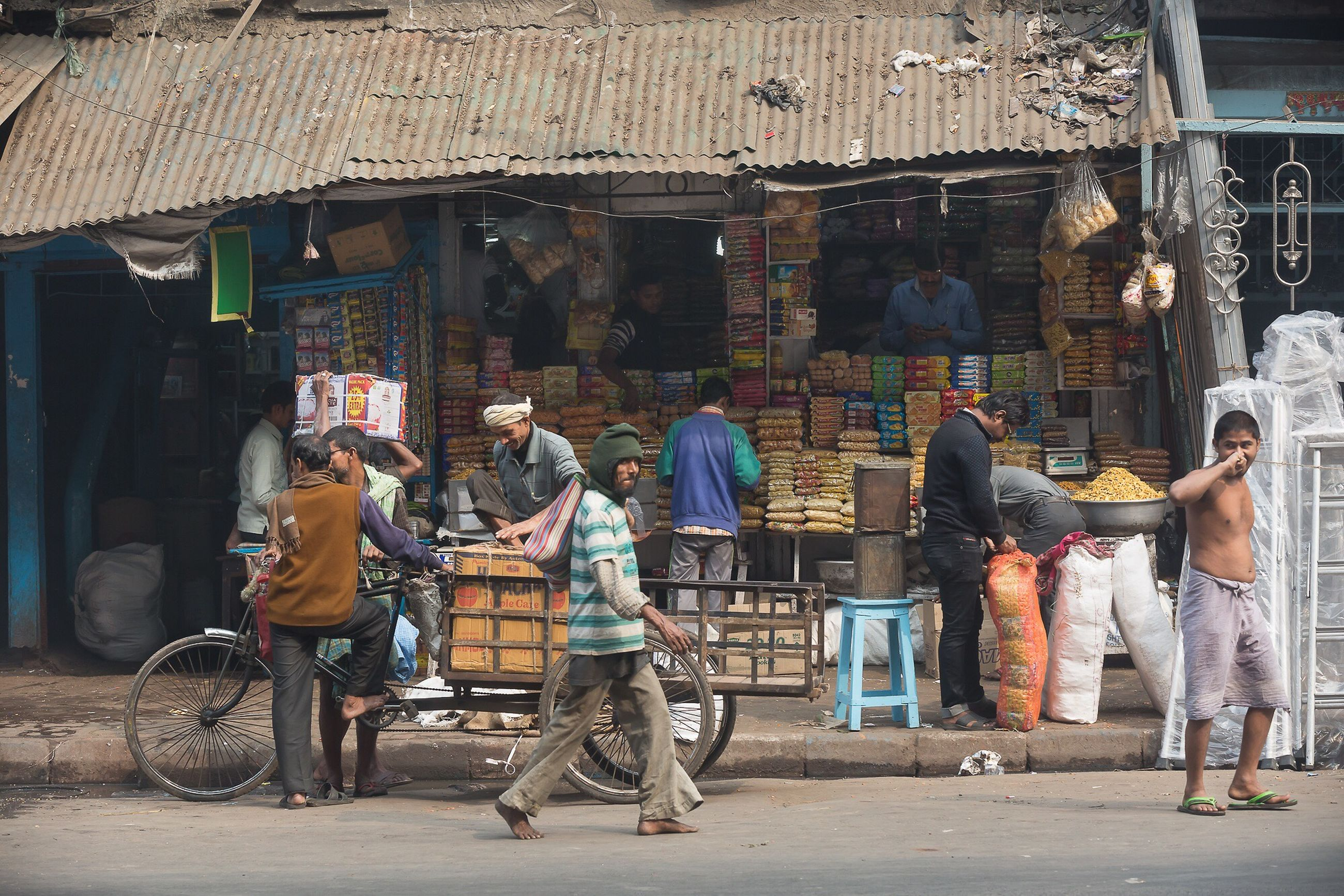 people, building exterior, architecture, built structure, lifestyles, street, full length, casual clothing, market, leisure activity, city, occupation, rear view, working, walking, outdoors, market stall