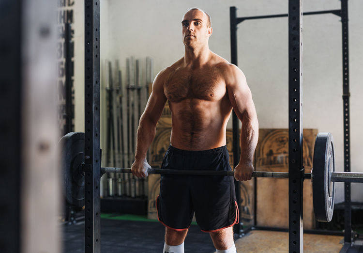 Shirtless Man Lifting Barbell In Gym