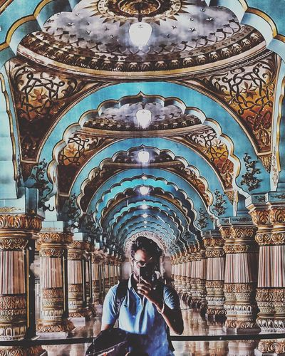 An asymmetrical figure in the midst of perfect symmetry. Mirror Mirror Selfie Mysore Palace Symmetry Ceiling Ceiling Light  Men Place Of Worship Religion Architecture Historic Royalty Architecture And Art Architectural Design