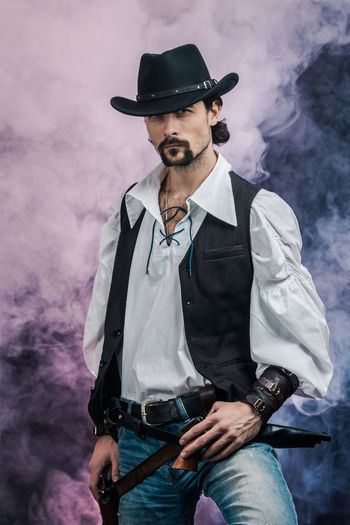 Handsome young man. This is an American cowboy. A vow to a white shirt, brown waistcoat and blue jeans. Black shoes on the feet. Carries a shtyapa, on a belt two pistols. The hair is of medium length; on the face is a beard and mustache. Authentic photo. Culture of America. Cowboy Wild West America American Gun National Authentic Moments Lifestyles Lifestyle One Person Candid Authentic Smoke - Physical Structure Hat Beard Three Quarter Length Facial Hair Front View Clothing Real People Smoke Young Adult Casual Clothing Social Issues Fashion