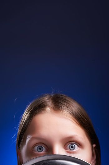 Portrait of young woman holding colander against blue background