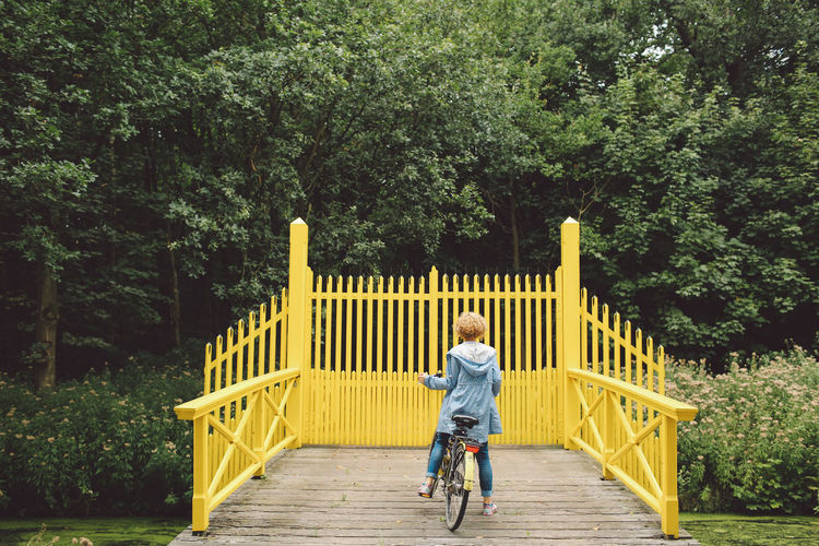 Rear view of woman riding bicycle on footbridge against trees