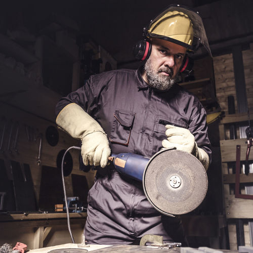 Portrait Of Manual Worker Working In Workshop