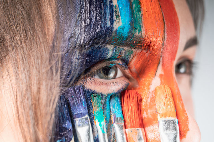 Close-up of young woman painting face