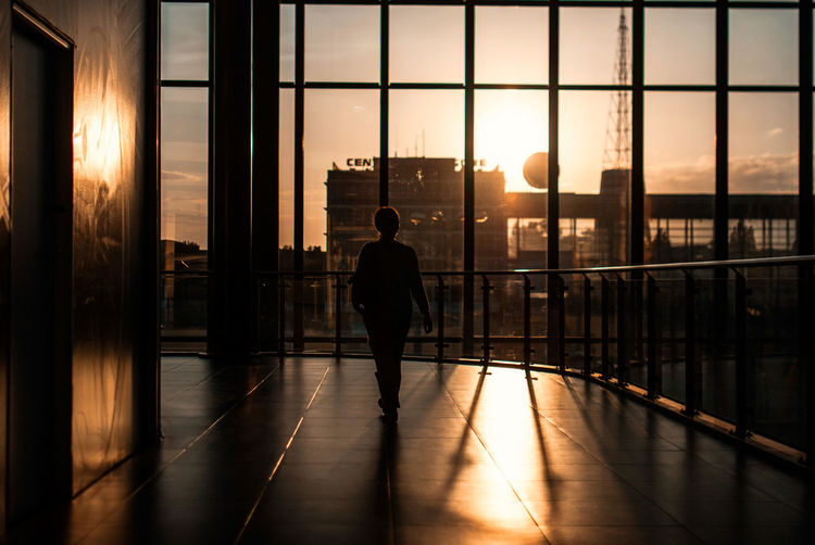 Silhouette Woman Walking In Corridor Of Modern Building Against Sunset