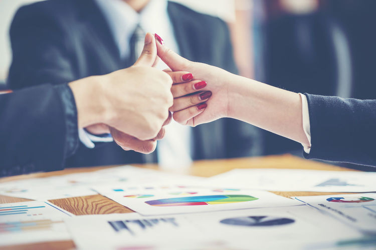 Business colleagues gesturing thumbs up over desk in office