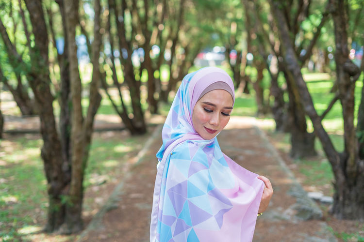 Portrait of lovely young Malay woman, modern stylish Muslim fashion, nature background. Selective focus. One Person Lifestyles Malaysia Malay ASIA Muslim Young Adult Attractive Fashion Modern Wood - Material Wood Forest Beauty In Nature Sky Tree Tranquility Stylish Style Plant People Real People Relaxing Close-up City Nature Mountain Day Hanging Out Growth Green Color Grass Travel Beautiful Portrait Smiling Women Hijab Focus On Foreground Leisure Activity Land Headscarf Adult Clothing Young Women Traditional Clothing Waist Up Outdoors Beautiful Woman