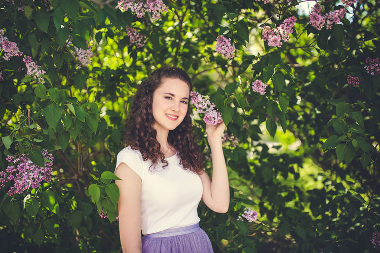 Happy curly hair young woman in a white t-shirt under the blooming lilac trees. smiling