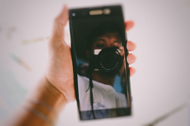 Reflection of man holding camera on mobile screen