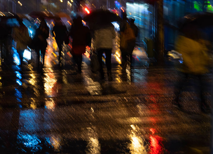 Group of people walking on wet road at night