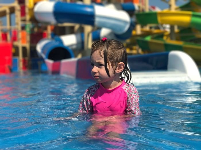 Girl looking away while swimming in pool at water park
