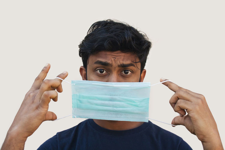 Portrait of young man making face against white background