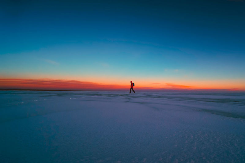 Man walking on snowy landscape against sky during sunset