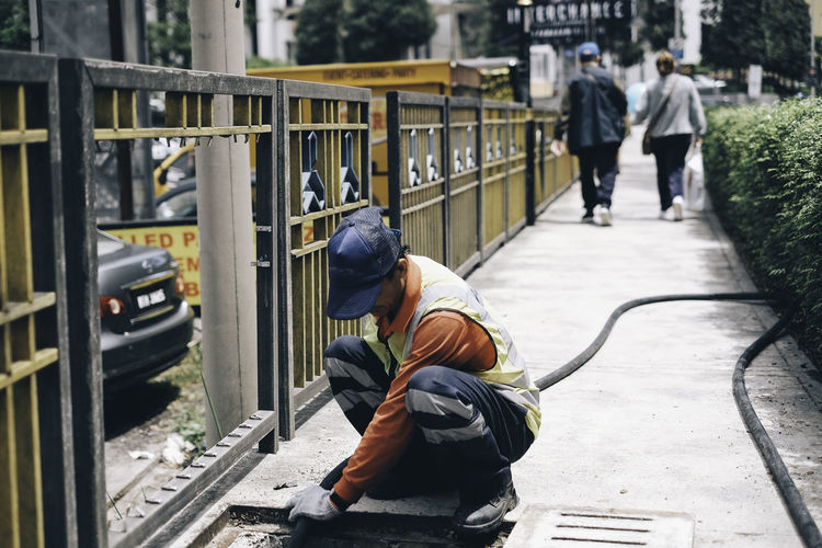 A worker maintaining a sewer Architecture BYOPaper! Day Full Length Maintenance Maintenance Engineer Maintenance Work Manual Worker Men Occupation One Person Outdoors People Real People Rear View Street Streetphotography The Street Photographer - 2017 EyeEm Awards Transportation Walking Working