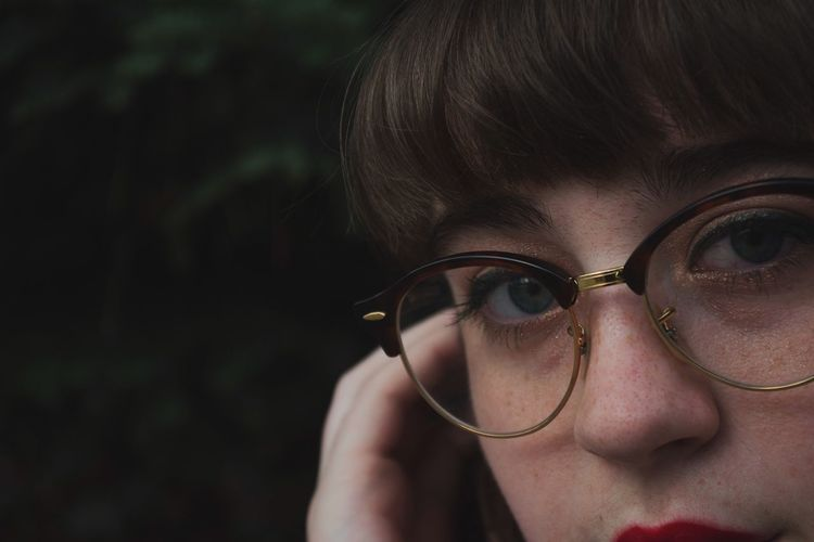 Close-up portrait of woman in eyeglasses outdoors