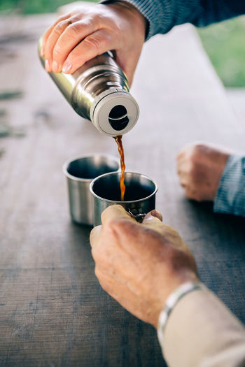 Close up of senior couple hands pouring coffee in a metal cup from thermos over a wooden table Coffee Couple Hands Hot Love Man Pouring Tea Thermos Wanderlust Woman Close Up Cup Drink Female Holding Lifestyles Male Metal Senior Table Togheter Two People Unrecognizable Vertical