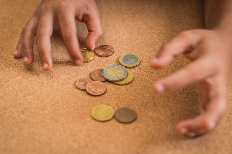Close-up of hands counting coins on table