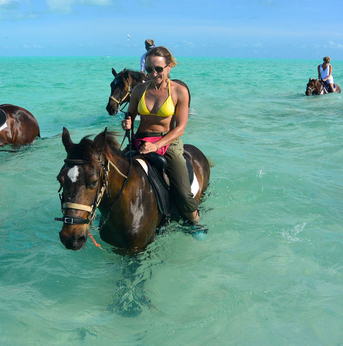 Woman sitting on horse in sea