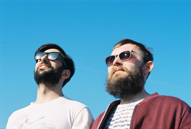 Peter and Stratos Beard Blue Clear Sky Facial Hair Fashion Glasses Headshot Leisure Activity Lifestyles Low Angle View Men Outdoors People Portrait Real People Sky Sunglasses Sunlight Young Adult Young Men