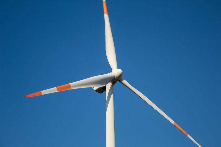 A close-up of the blades of a wind turbine, sky background