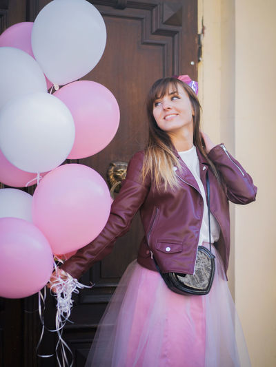 Smiling young woman holding pink balloons while standing against door